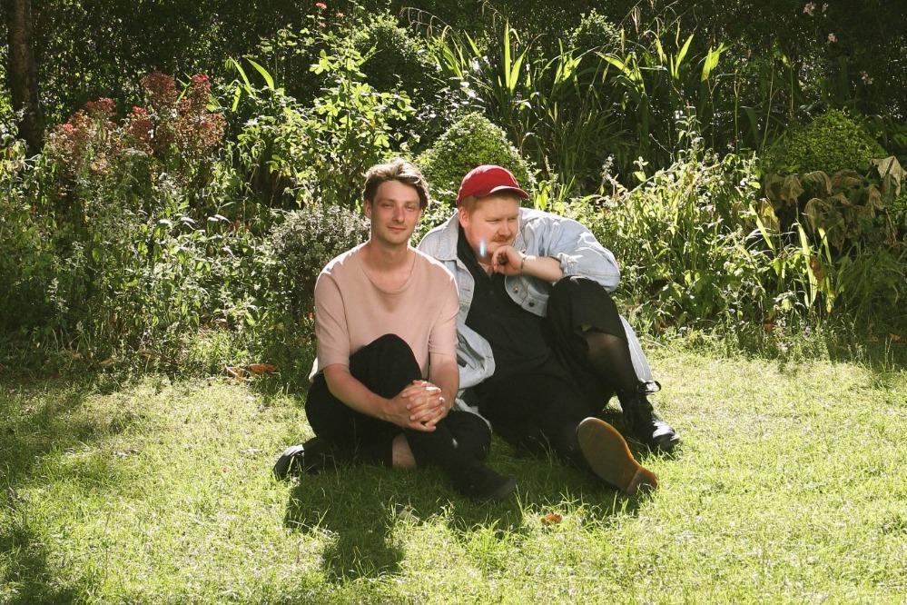 Le duo Her's assis sur l'herbe au Soleil