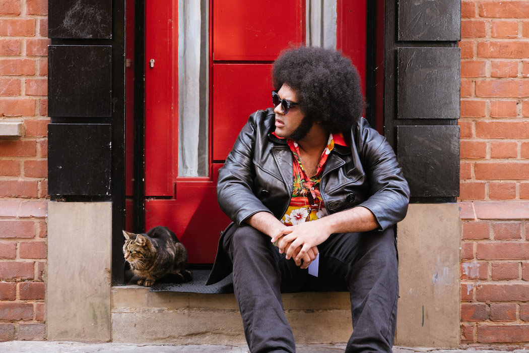 Rapper Dylan Cartlidge sitting outside in front of a red door