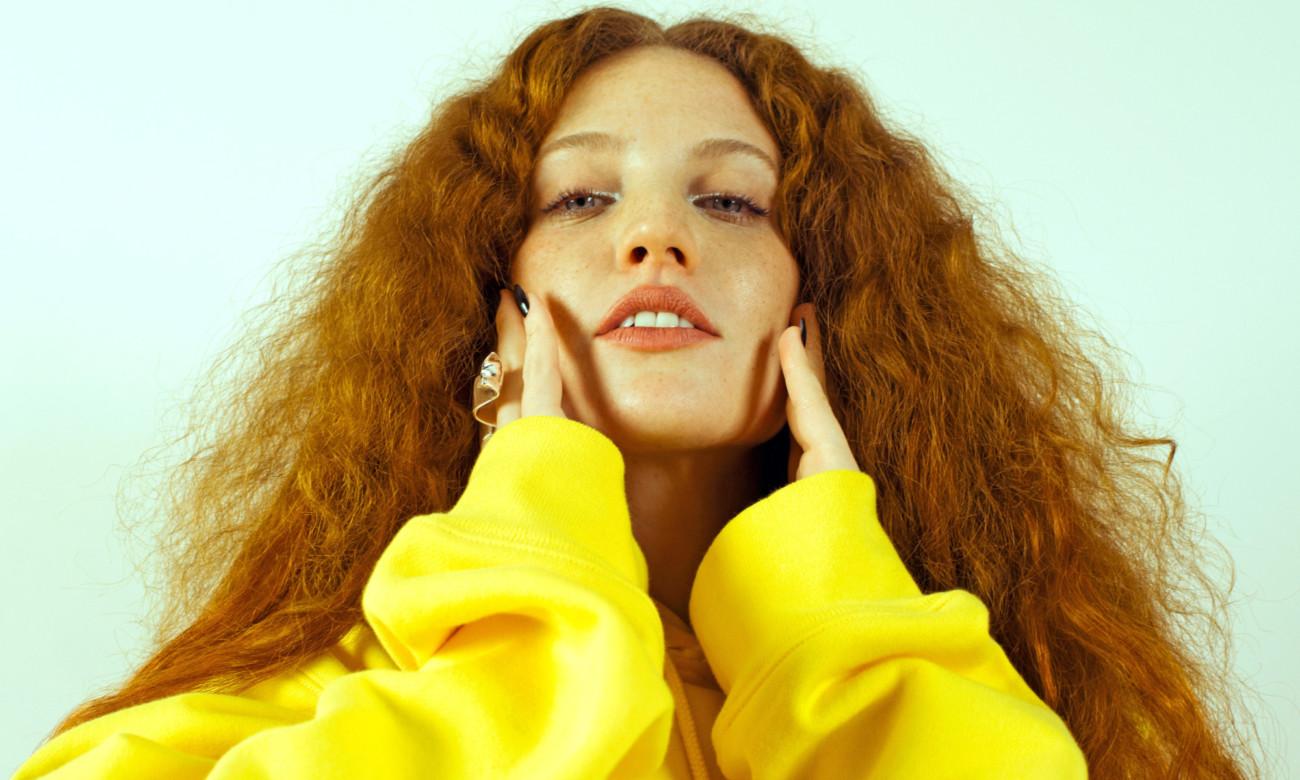 Jess Glynne, une femme aux longs cheveux roux ondulés, avec un sweat jaune