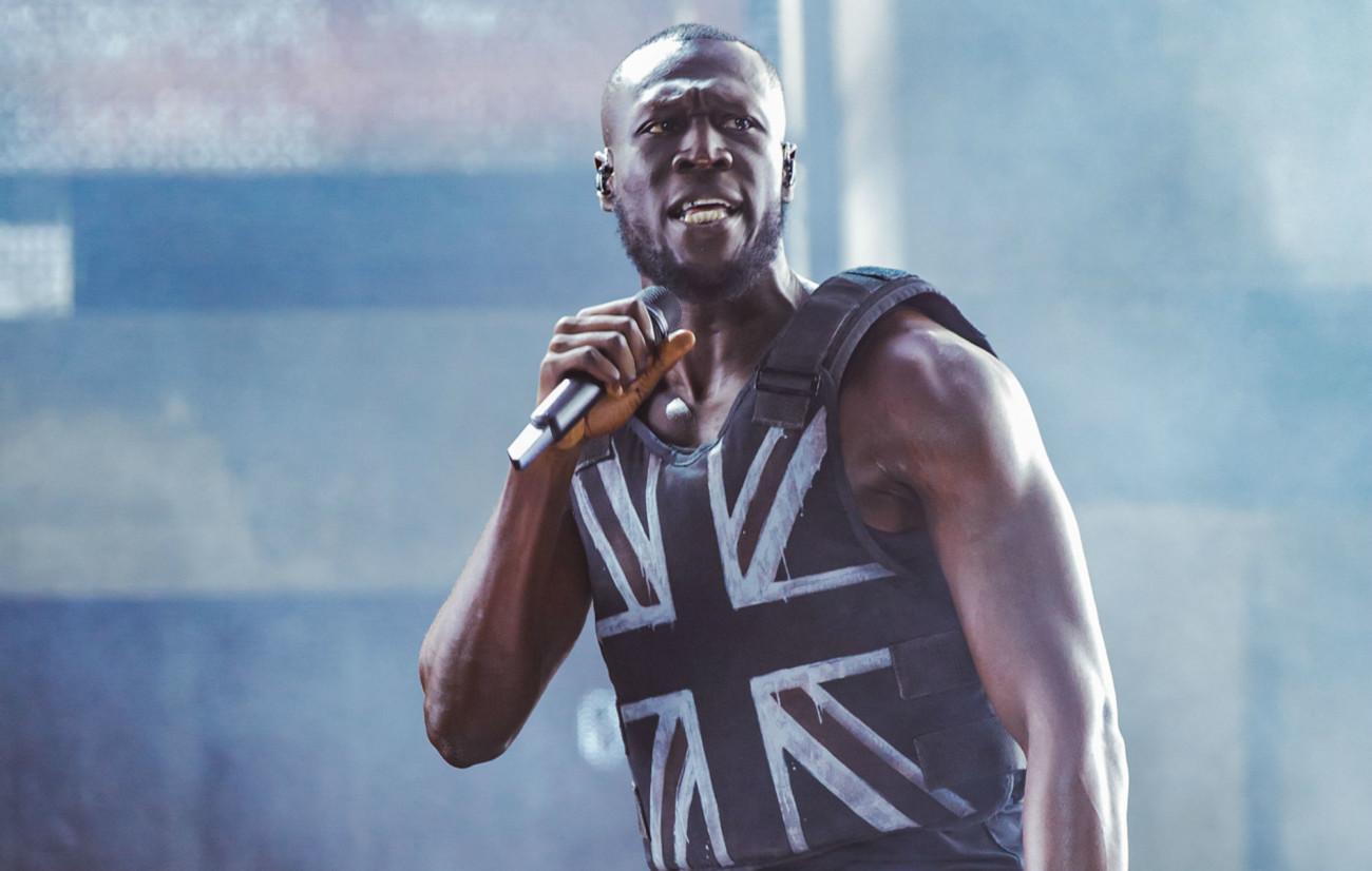 Stormzy, un rappeur anglais noir, sur la scène de Glastonbury avec un gilet sur lequel est peint l'Union Jack