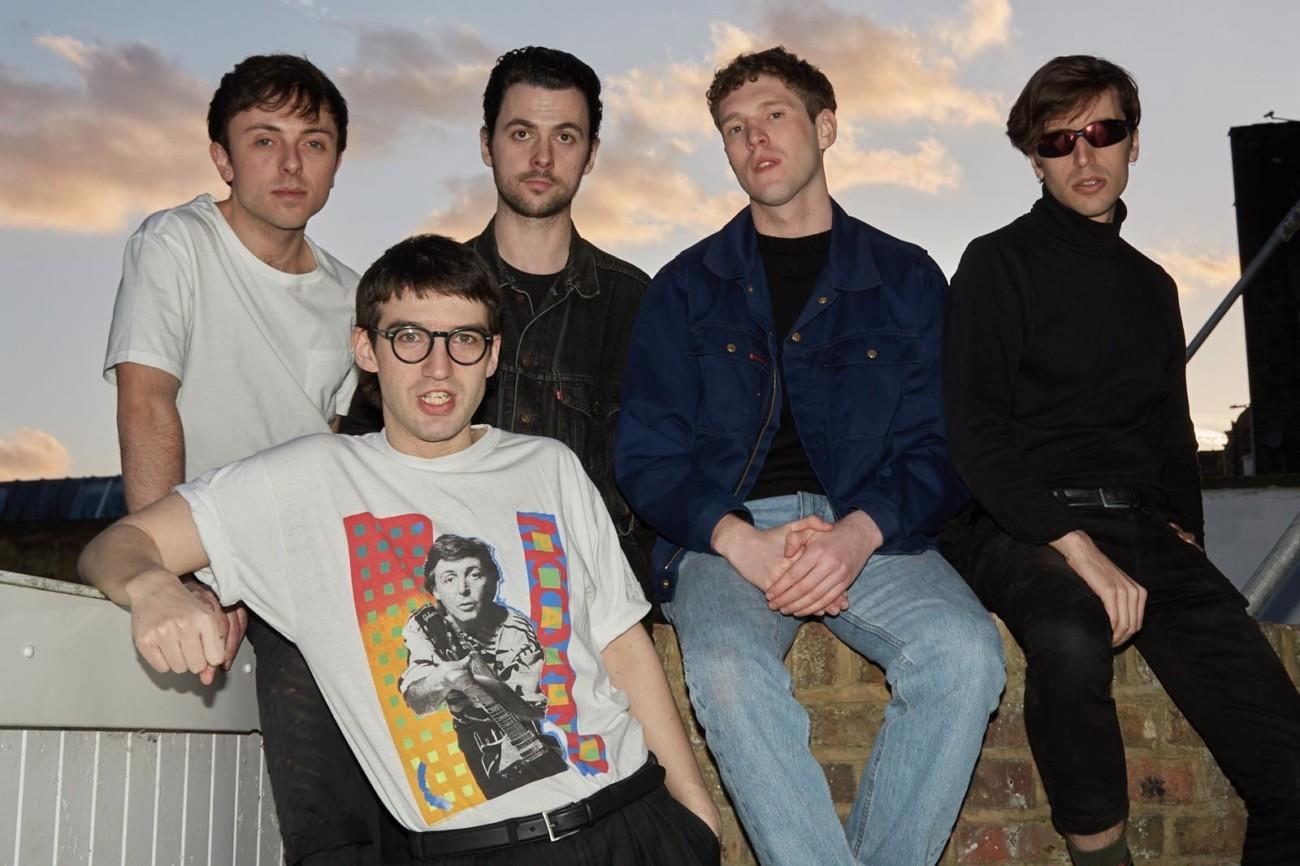 Le groupe Spector, composé de cinq hommes, assis sur un muret