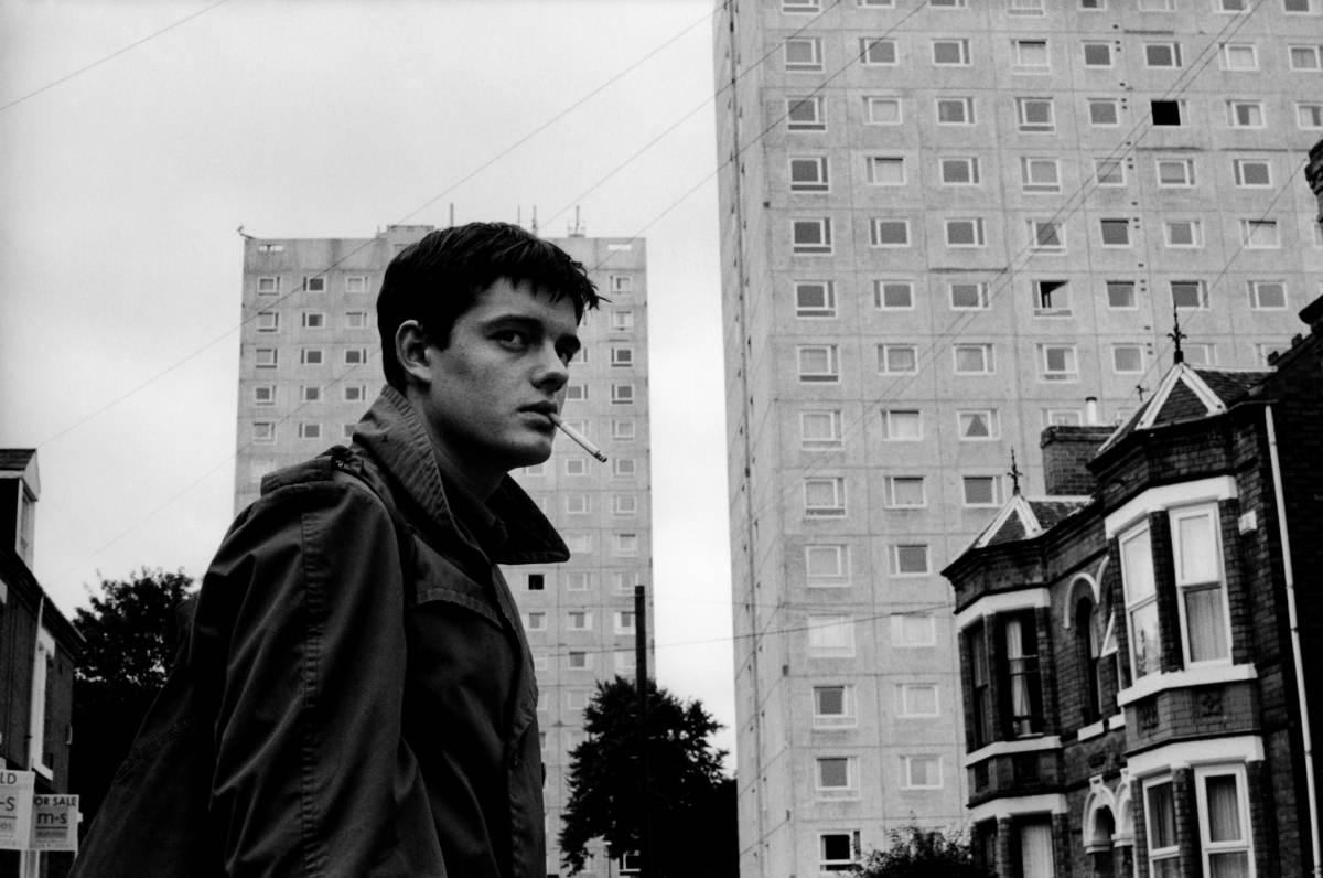 Ian Curtis devant des immeubles. Photo en noir et blanc