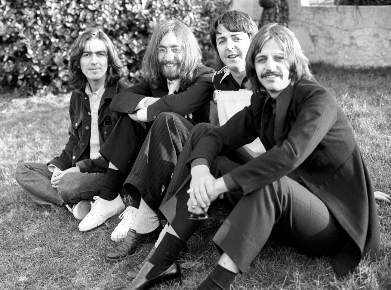 The Beatles assis sur l'herbe en 1969